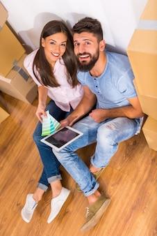 Młoda szczęśliwa para przygotowuje się do naprawy w nowym domu.