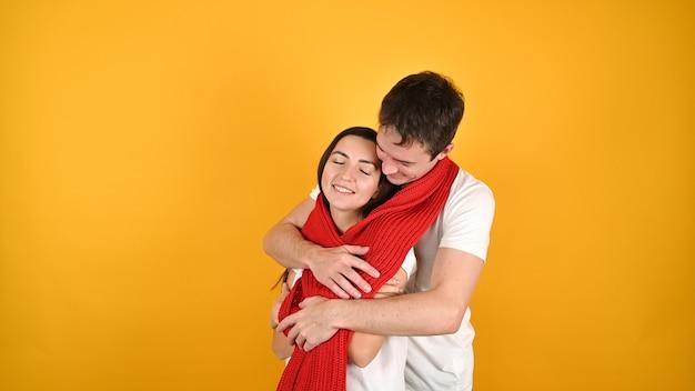 Młoda szczęśliwa para przytula się na żółto