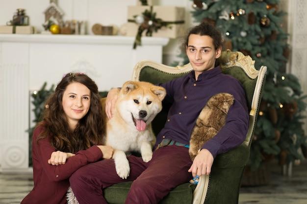 Młoda szczęśliwa para przytula uroczego psa akita inu, siedząc na stylowym fotelu retro na święta bożego narodzenia w domu.