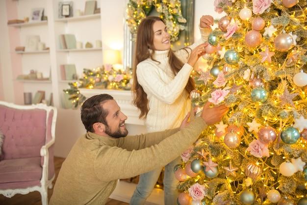 Młoda szczęśliwa para razem dekorowanie choinki