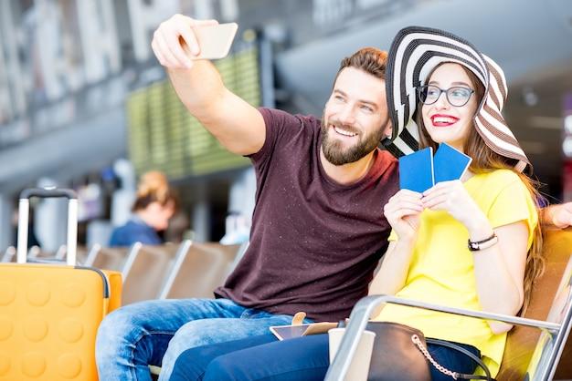 Młoda szczęśliwa para robi selfie zdjęcie z telefonem w poczekalni lotniska podczas letnich wakacji