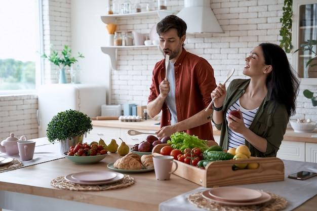 Młoda szczęśliwa para rodzinna tańczy śpiewając i bawiąc się przygotowując zdrowe jedzenie w nowoczesnym stylu