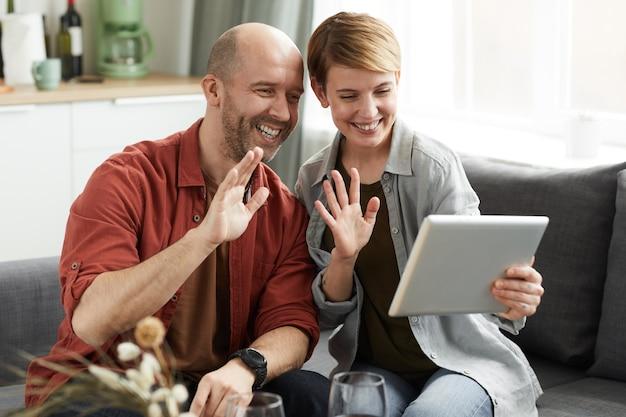 Młoda szczęśliwa para siedzi na kanapie i przy użyciu cyfrowego tabletu do rozmowy online macha i uśmiecha się