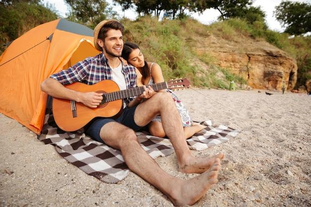 Młoda szczęśliwa para siedzi w namiocie i gra na gitarze na plaży