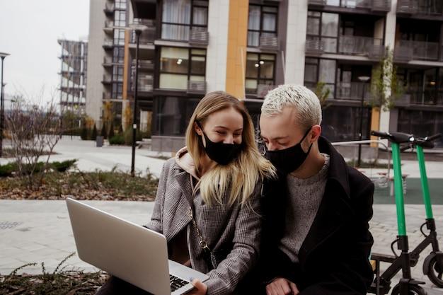 Młoda szczęśliwa para spędza miło czas na ławce w pobliżu bloków mieszkalnych. oglądają filmy i się śmieją. blondynka i stylowy mężczyzna w maskach na twarz, trzymając laptopa i rozmawiając.