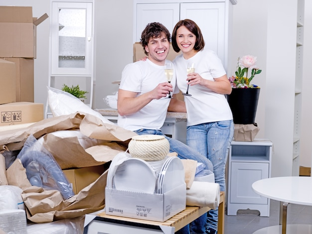 Młoda szczęśliwa para świętuje nowy dom wraz z lampką szampana - w pomieszczeniu