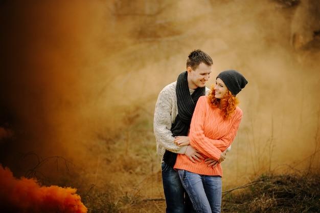 Młoda szczęśliwa para trzyma dymne bomby na campingu