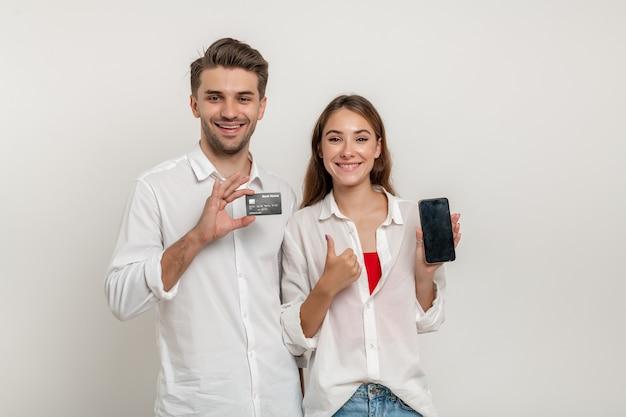 Młoda szczęśliwa para trzyma kredytową kartę bankową za pomocą smartfona z kciukiem do góry na białym tle