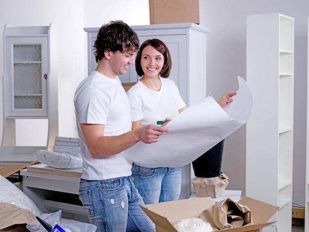 Młoda szczęśliwa para trzyma projekt z ich przyszłym nowym mieszkaniem