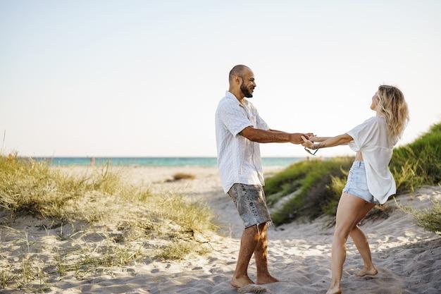 Młoda szczęśliwa para trzymając się za ręce i idąc razem na plażę w letni dzień
