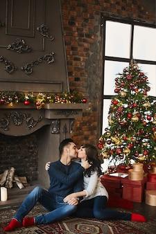 Młoda szczęśliwa para, w ciepłych swetrach i czerwonych skarpetkach, przytulająca się i siedząca na autentycznym dywanie przy kominku i choince. boże narodzenie i nowy rok. świąteczny nastrój.