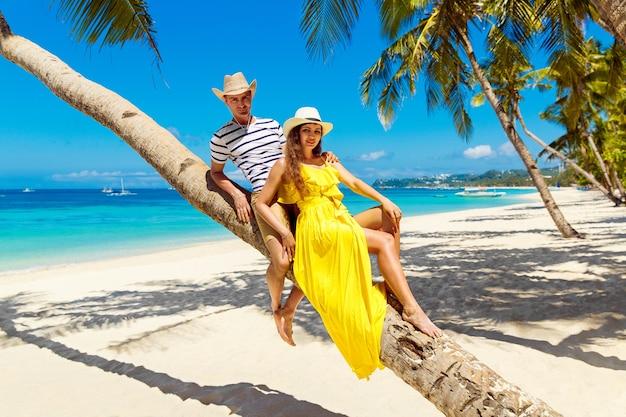 Młoda szczęśliwa para w kapeluszach siedzi na drzewie kokosowym na tropikalnej, piaszczystej plaży. koncepcja podróży i wakacji.