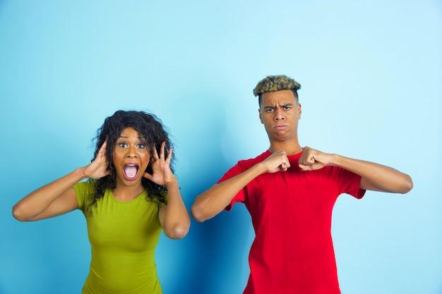 Młoda szczęśliwa para w ubranie, pozowanie na niebieskiej ścianie