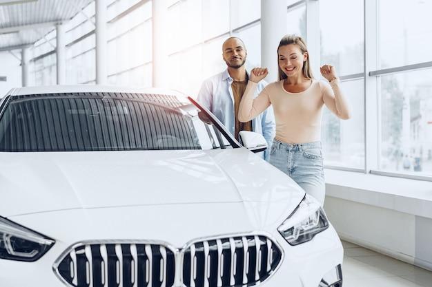 Młoda szczęśliwa para wybiera nowy samochód w salonie samochodowym