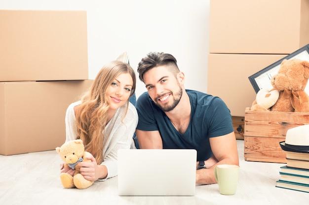 Młoda szczęśliwa para z tabletem pc i ruchomymi pudełkami siedzącymi na podłodze w nowym domu