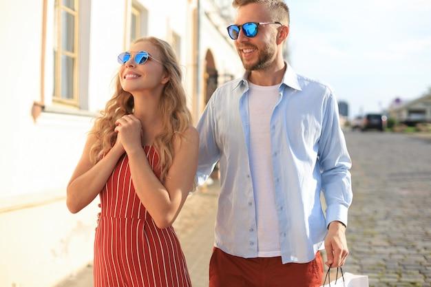 Młoda szczęśliwa para z torby na zakupy w mieście.