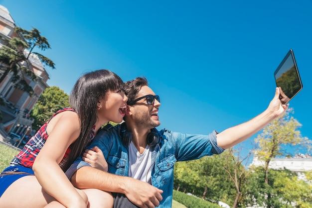 Młoda szczęśliwa para za pomocą tabletu, siedząc w parku