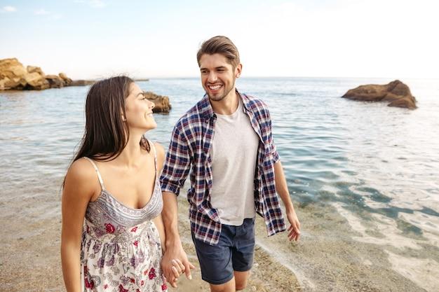 Młoda szczęśliwa para zakochana spacerująca po plaży trzymająca się za ręce