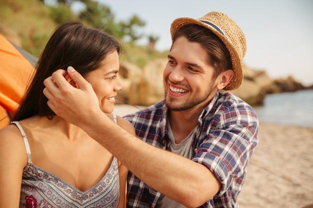 Młoda szczęśliwa para zakochana w objęciach siedząc przy namiocie na plaży