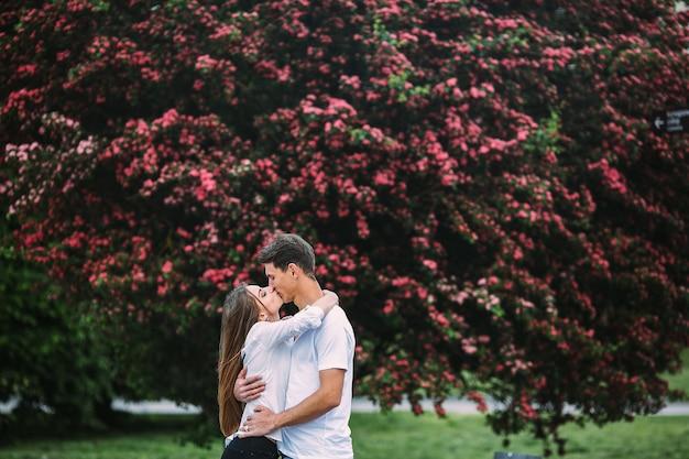 Młoda szczęśliwa para zakochanych na zewnątrz. kochający mężczyzna i kobieta na spacerze w kwitnącym wiosną parku