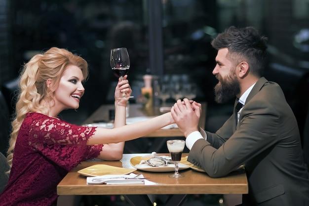 Młoda szczęśliwa para zakochanych siedzi w kawiarni.