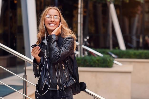 Młoda szczęśliwa piękna dziewczyna w wielkomiejskim słucha muzyki w słuchawkach. radosna dziewczyna idzie ulicą.