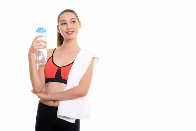Młoda szczęśliwa piękna kobieta azji uśmiecha się i myśli, trzymając butelkę wody gotowy do siłowni