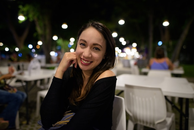 Młoda szczęśliwa piękna kobieta azji uśmiecha się podczas siedzenia