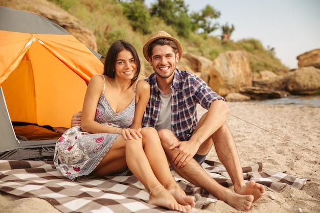 Młoda Szczęśliwa Piękna Para Siedzi W Namiocie Na Plaży Premium Zdjęcia