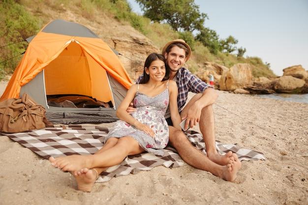 Młoda szczęśliwa piękna para siedzi w namiocie na plaży