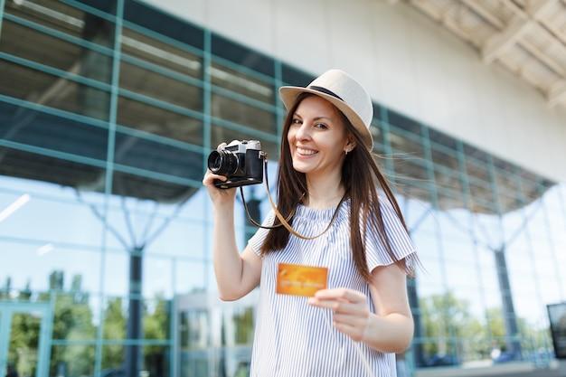 Młoda szczęśliwa podróżniczka turystyczna kobieta w kapeluszu trzyma aparat retro vintage, karta kredytowa na międzynarodowym lotnisku