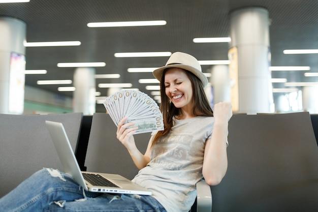 Młoda szczęśliwa podróżniczka turystyczna kobieta z laptopem trzyma pakiet dolarów gotówki, robi gest zwycięzcy, czekaj w holu na lotnisku