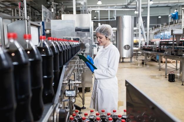 Młoda szczęśliwa pracownica w fabryce butelkowania sprawdzająca butelki soku przed wysyłką