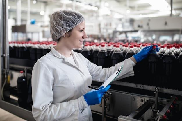 Młoda szczęśliwa pracownica w fabryce butelkowania sprawdzanie butelek soku przed wysyłką. kontrola jakości inspekcji.