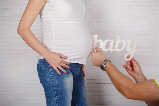 """Młoda szczęśliwa rodzina czeka na narodziny dziecka. 9 miesięcy zdrowej ciąży i macierzyństwa z bliska. słowo kobieta """"dziecko"""" w rękach mężczyzny. mężczyzna trzyma napis """"dziecko"""" przy brzuchu kobiety w ciąży"""
