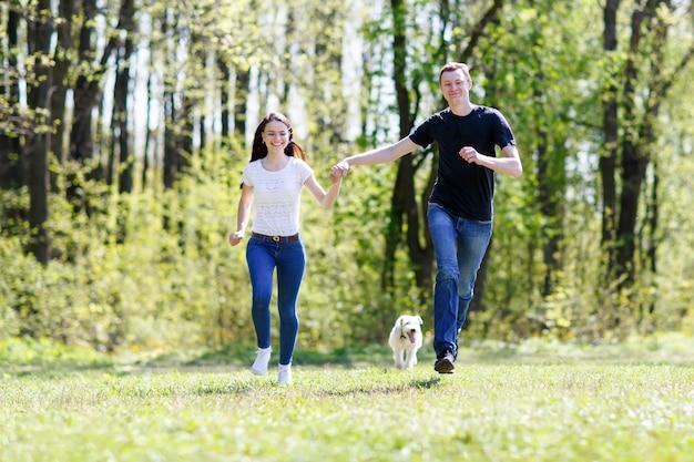 Młoda szczęśliwa rodzina działa z psem na zielonej łące