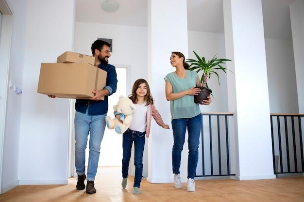 Młoda szczęśliwa rodzina gospodarstwa pudełka i kwiat podczas przeprowadzki do nowego domu.
