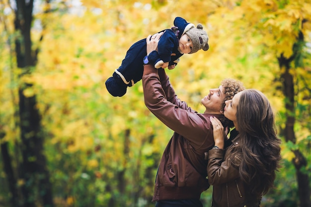 Młoda szczęśliwa rodzina jesienią w parku. ojciec radośnie wyrzuca syna.