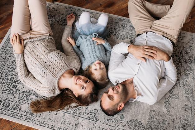 Młoda szczęśliwa rodzina leżąc na podłodze, baw się dobrze i uśmiechając się
