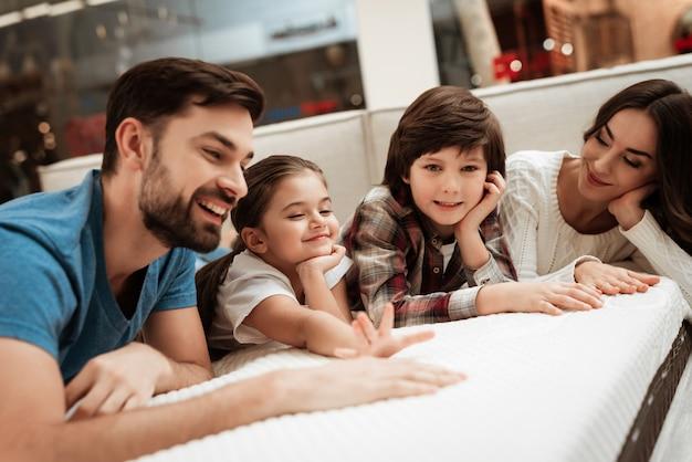 Młoda szczęśliwa rodzina relaks na miękkim łóżku w sklepie