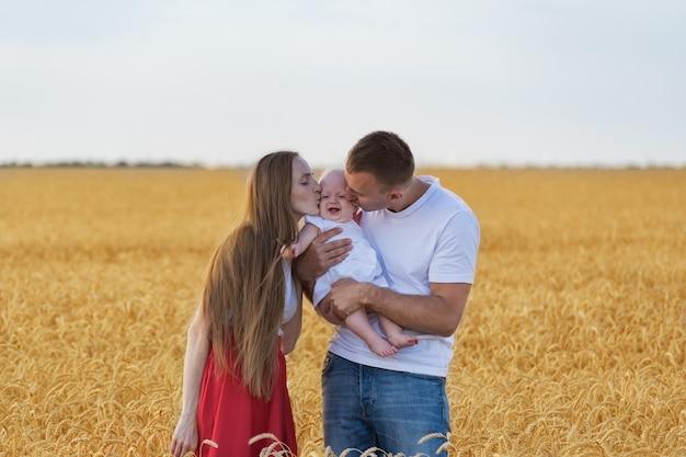 Młoda szczęśliwa rodzina w pszenicznym polu. mama i tata całują dziecko