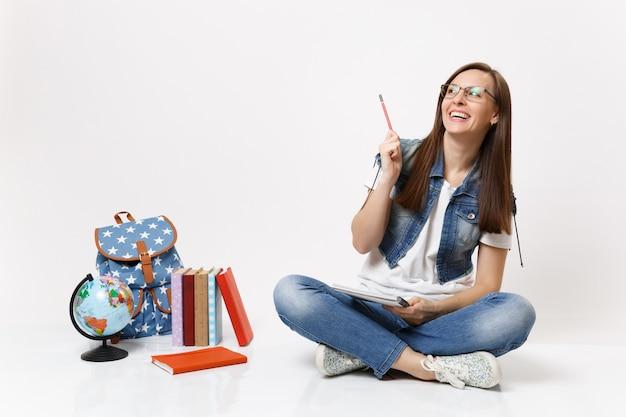 Młoda szczęśliwa roześmiana studentka w okularach wskazująca ołówek w górę trzymająca notebooka siedzącego w pobliżu kuli ziemskiej, plecaka, podręczników szkolnych na białym tle