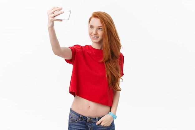Młoda szczęśliwa ruda kobieta izolowanych ponad białym tle ściany zrobić selfie