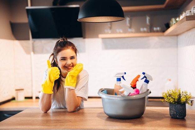 Młoda szczęśliwa śliczna kobieta w żółtych rękawiczkach czyści kuchnię w domu z detergentami