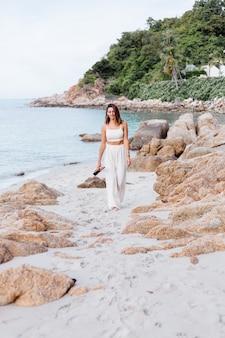 Młoda szczęśliwa spokojna kaukaski kobieta z ukulele na tropikalnej kamienistej plaży o zachodzie słońca
