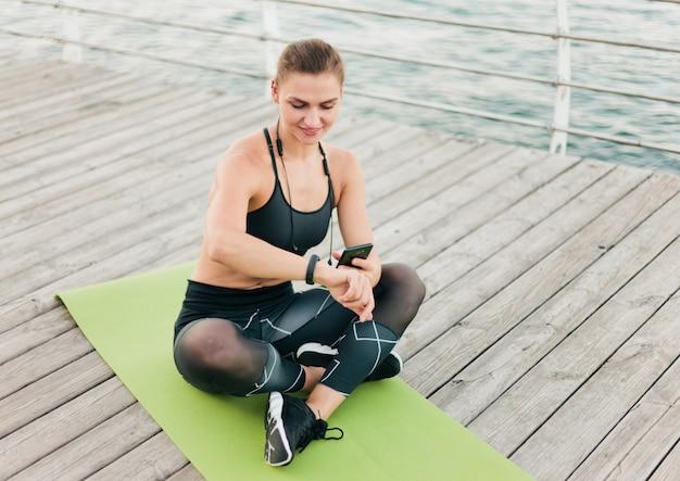 Młoda szczęśliwa sport kobieta używa smartphone i mądrze bransoletkę podczas gdy siedzący na macie przy drewnianym tarasem na plaży.