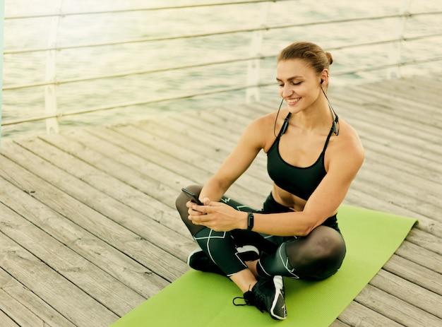Młoda szczęśliwa sportowa kobieta, słuchanie muzyki przez słuchawki i używanie smartfona, siedząc na macie na drewnianym tarasie na plaży