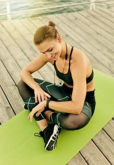 Młoda szczęśliwa sportowa kobieta używa inteligentnej bransoletki, siedząc na macie na drewnianym tarasie na plaży