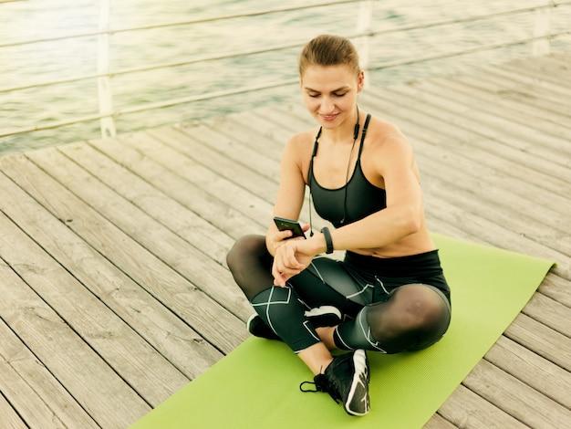 Młoda szczęśliwa sportowa kobieta używa smartfona i inteligentnej bransoletki, siedząc na macie na drewnianym tarasie na plaży
