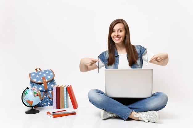 Młoda szczęśliwa studentka dorywcza wskazująca palcem wskazującym na laptopie i siedząca w pobliżu kuli ziemskiej, plecaka, podręczników szkolnych na białym tle